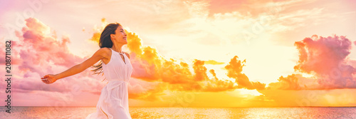 plakat Well being free woman with open arms in the air blissful happiness concept banner. Happy woman against pink pastel colorful sunset sky.
