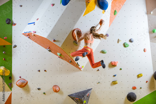 Photo Young woman jumping on handhold in bouldering gym
