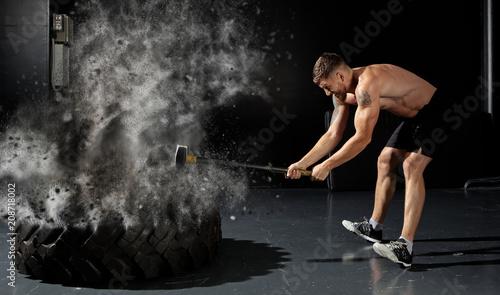 Fotografia man hitting wheel tire with hammer sledge