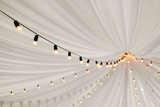 Fototapeta Perspektywa 3d - Garlands of lamps on a cord in a white tent. A wedding Banquet.