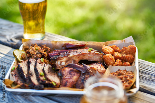 Poster Buffet, Bar tray of smoked meats texas bbq style outside on picnic table on sunny summer day