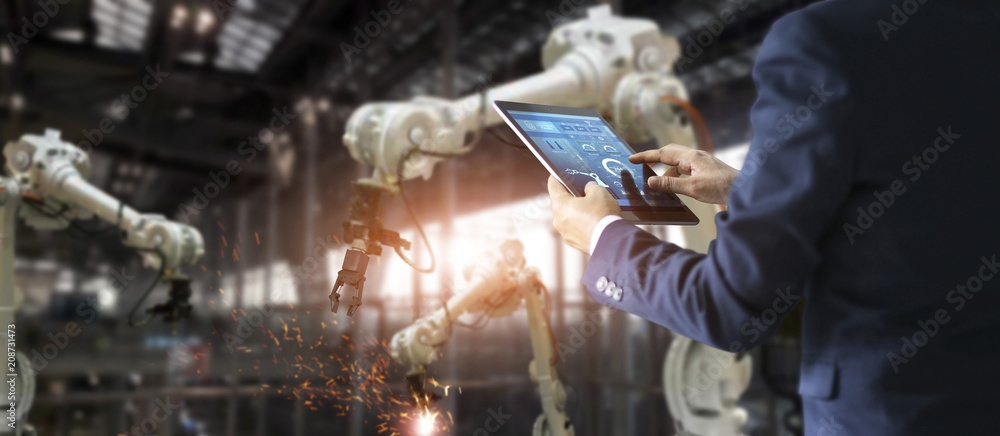 Fototapeta Industrial engineer manager using tablet control automation robot arms machine in intelligent on monitoring. Welding robotics and digital manufacturing operation. Industry 4.0 concept