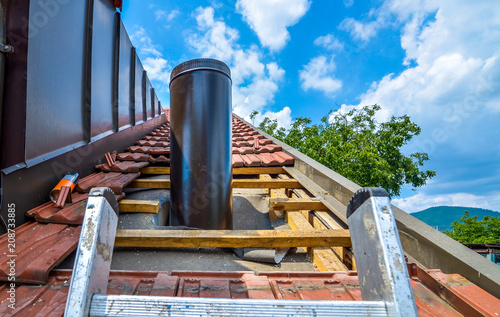 Fotografia Installing external chimney trough a house roof with roof tiles.