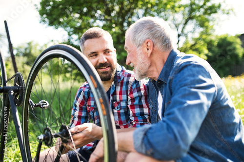 Fotobehang Sportwinkel An adult hipster son and senior father repairing bicycle outside on a sunny day.