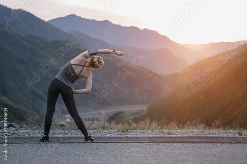 Fotografia  Athlete at the top of the mountain doing workout.