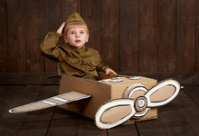 Children Boy Are Dressed As Soldier In Retro Military Uniforms Sit In An Airplane Made Of Cardboard Box And Dreams Of Becoming A Pilot, Dark Wood Background, Retro Style