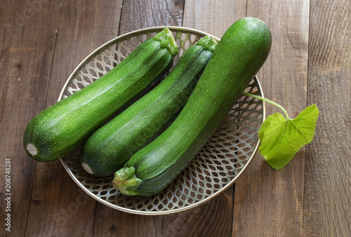 three ripe gardening green oblong zucchini on the table