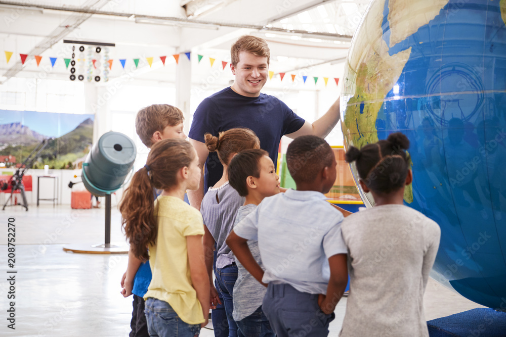 Fototapety, obrazy: School kids looking at a giant globe at a science centre