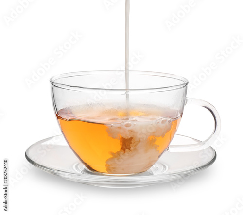 Stickers pour porte The Pouring milk into glass cup with aromatic tea on white background