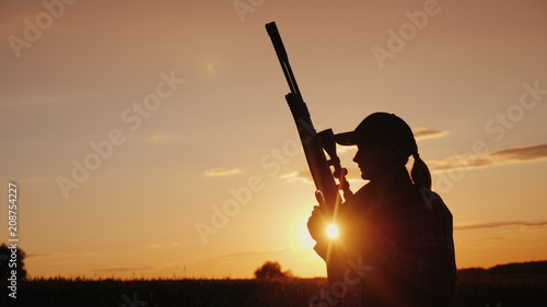 Fotografía Beautiful silhouette of a woman with a rifle in the rays of the setting sun