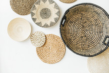 Decorative Straw Plates On White Wall.