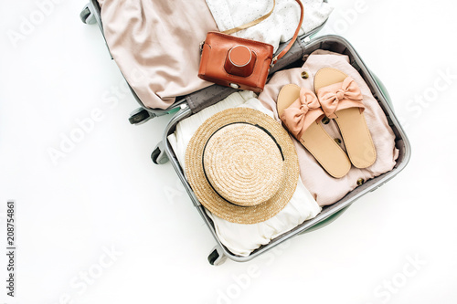 Hand luggage with stylish female clothes and retro camera on white background. Flat lay, top view. Summer fashion clothes and travel concept. - fototapety na wymiar
