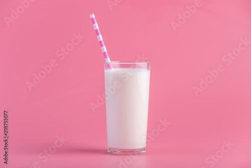 Obraz na płótnie Glass of fresh milk with a straw on a pink background