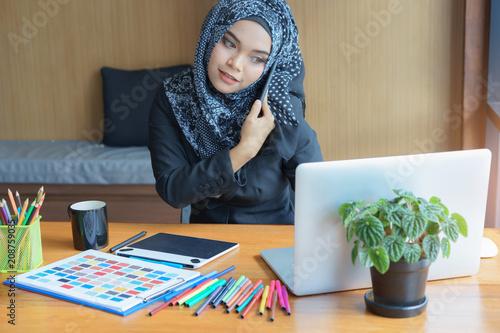 Fotografía  Busy asian muslim business woman talking on mobile phone in modern office
