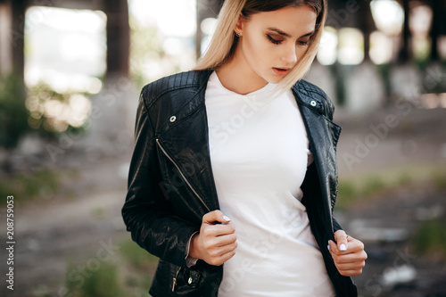 Girl wearing t,shirt and leather jacket posing against