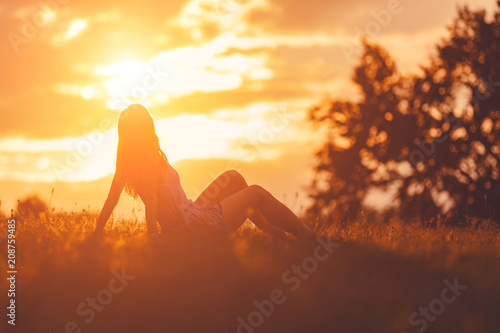Fotografia  Girl enjoying in the meadow at golden sunset time.