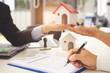 Real estate agent holding a house to his client and signing contract agreement in office,concept for real estate, moving home or renting property