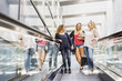 Three young women on escalator