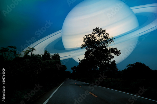 Saturn near earth on night sky over the country road