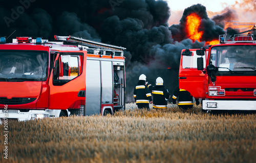 Tablou Canvas Red fire trucks in front of huge black smoke from the fire