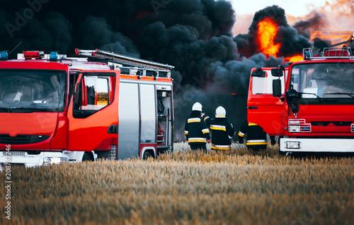 Fototapeta Red fire trucks in front of huge black smoke from the fire