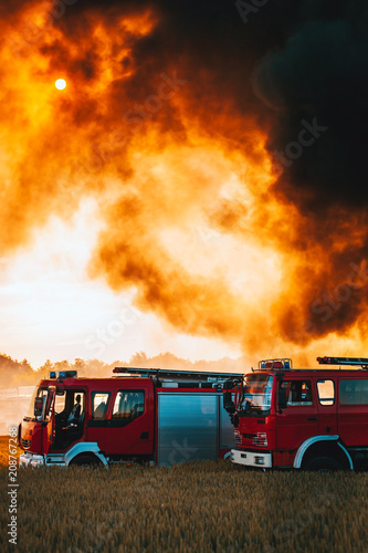 Fotografering Red fire trucks in front of huge black smoke from the fire