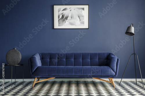 Fotografia, Obraz  Navy blue room interior with comfortable plush couch in the middle, black lamp and side table with decoration standing on chessboard floor