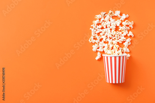 Paper bucket with scattered tasty popcorn on color background Wallpaper Mural