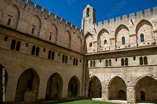 Fototapeta View of courtyard and internal buildings of the Palace of the Popes of Avignon, under a sunny blue sky. Located in the Vaucluse department, Provence-Alpes-Côte d'Azur region, southeastern France obraz