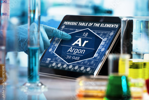 chemist consulting on the digital tablet data of the chemical element Argon Ar / Wallpaper Mural