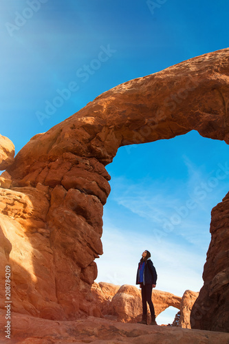 Fotografia Young woman traveler with backpack hiking the Turret Arch, Arches National Park