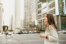 Beautiful Young Woman On The Boulevard In Urban Scenery, Downtown, At Sunset, Holding Smartphone