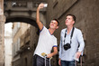 Two men with luggage doing selfie during city tour at vacation