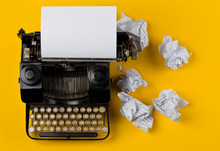 Vintage Typewriter Top Down Flatlay Shot From Above With Empty, Blank Sheet Of Paper And Crumbled Paper Balls On Yellow