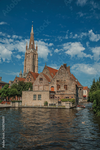 Tuinposter Brugge Steeple and old brick buildings on the canal's edge in a sunny day at Bruges. With many canals and old buildings, this graceful town is a World Heritage Site of Unesco. Northwestern Belgium.