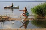 Fototapeta Fototapety z morzem do Twojej sypialni - Uśmiechnięta dziewczynka wrzuca kamienie do wody jeziora, mężczyzna na łodzi.