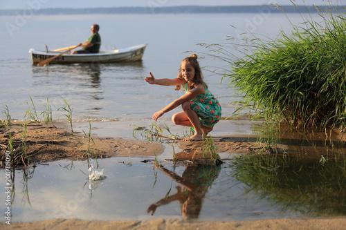 Fototapeta Uśmiechnięta dziewczynka wrzuca kamienie do wody jeziora, mężczyzna na łodzi. obraz