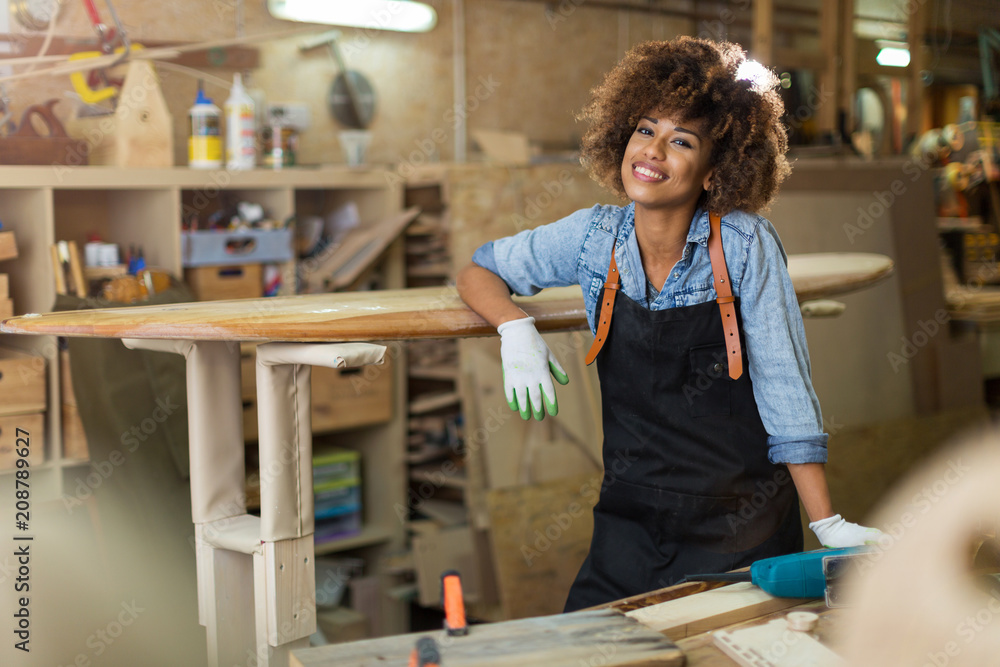 Fototapety, obrazy: Happy young woman working on surfboard in her workshop