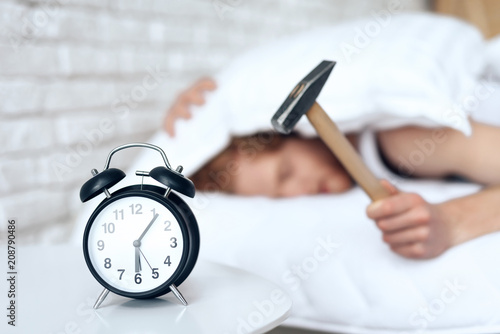 Photo Young red haired man hammers alarm clock.