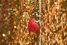 Red Metal Heart On A Golden Background. Soft Focus. Love And Valentine Concept. Lots Of Shining Sparkles On A Background.