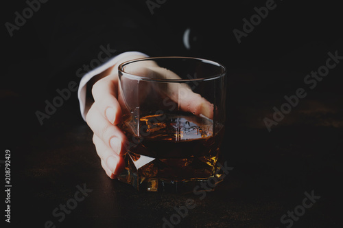 Glass with whiskey in hand, dark background, selective focus