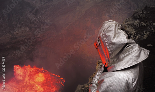 Foto op Aluminium Vulkaan A volcanologist stands in dangerous proximity to a crater with molten lava in a thermo-suit