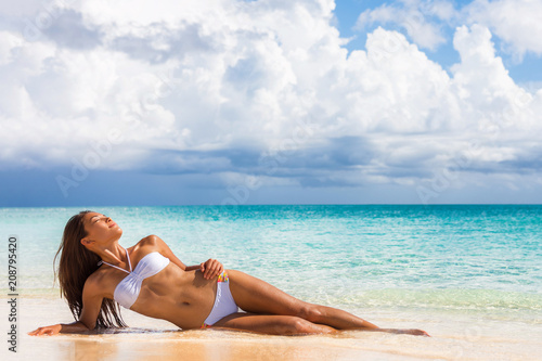 Obraz Sexy fashion bikini woman sunbathing lying down on white sand beach relaxing showing off toned abs and slim body. Asian model on tropical travel summer holidays - fototapety do salonu