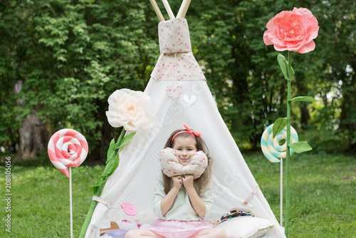 Foto Little girl lying and playing in a tent, children's house wigwam in park