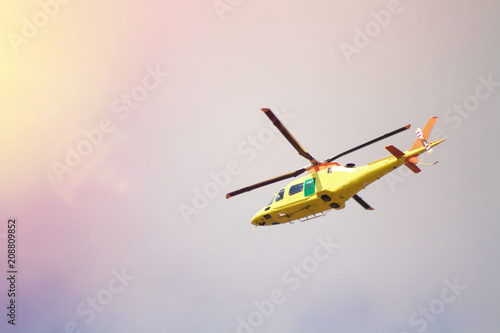 Foto op Plexiglas Helicopter Yellow helicopter flying low above the ground against the sky