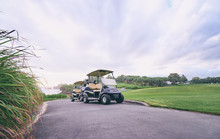 The Golf Course Landscape With Beautiful Sky. Golf Carts At The Green Golf Course.