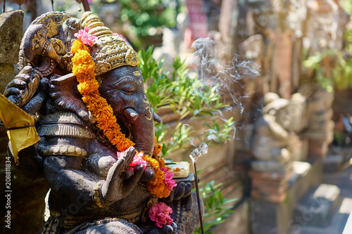 Religious decoration. Traditional stone sculpture of Ganesha god with flowers in the backyard. Bali, Indonesia.