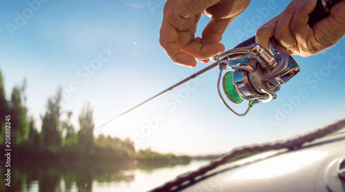 Fishing background. Fisherman with spinning on the lake.