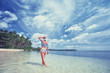 Vacation on the seashore. Back view of young woman walking away on the beautiful tropical white sand beach.