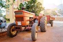 Old Orange Tractor On Town Street.